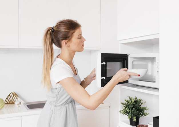 blonde-young-woman-inserting-bowl-microwave