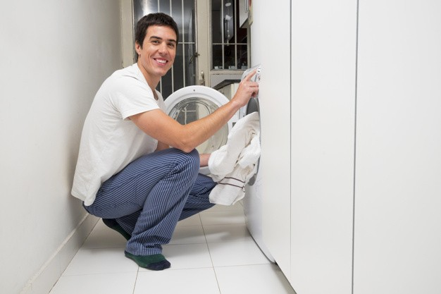 smiling-young-man-putting-clothes-washing-machine