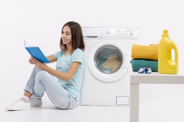 woman-reading-near-washing-machine