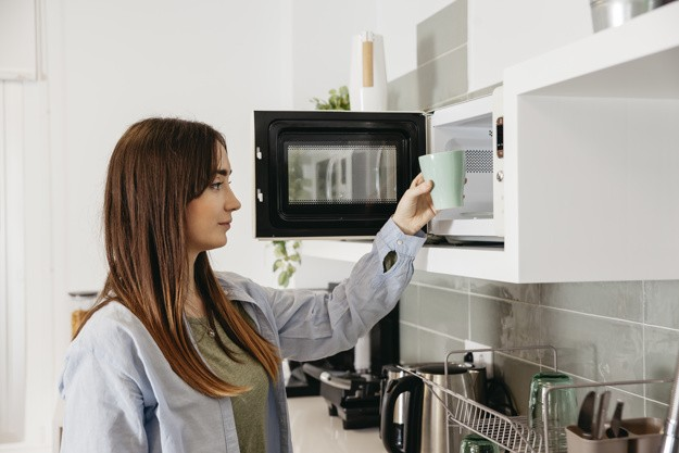 casual-girl-using-microwave-heat-cup