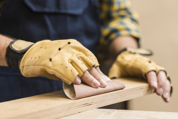 male-carpenter-smoothing-wooden-plank-with-sandpaper