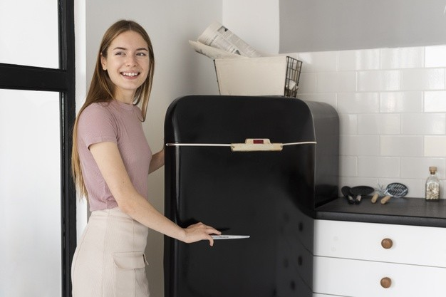smiley-woman-opening-black-fridge
