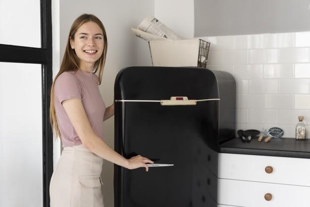 smiley-woman-opening-black-fridge